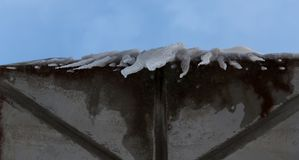 Dangerous ice on the roof. Some dangerous Icicles hanging from the roof with the sky in the background Stock Photography