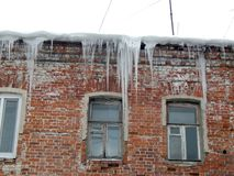 Dangerous icicles dangling from the roof of houses Stock Photography