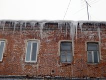 Dangerous icicles dangling from the roof of houses Royalty Free Stock Image