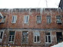 Dangerous icicles dangling from the roof of houses Stock Photos