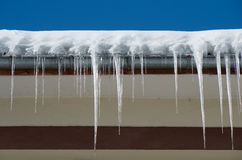 Dangerous icicles. Fines for snow and ice on roofs. Royalty Free Stock Image