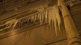Dangerous icicles hang from the snowy roof of building stock footage