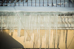 Dangerous icicles in a house roof. Big dangerous icicles hanging from the roof of the house Royalty Free Stock Photography