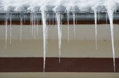 Dangerous icicles in a house roof. Dangerous icicles. Fines for snow and ice on roofs Stock Photos