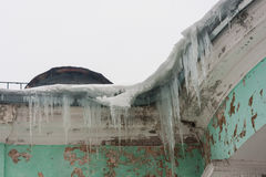 Dangerous icicles in a house roof. Dangerous large icicles in a house roof Royalty Free Stock Images