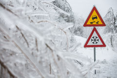 Dangerous and icy road sign. With sleet covered trees. Danger on the road, black ice danger, wintertime concept Royalty Free Stock Images