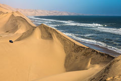 Dangerous jeep - safari. Ocean surf with foamy waves. Dangerous jeep - safari through the huge sand dunes. Atlantic coast of Walvis Bay, Namibia, south of Africa stock image