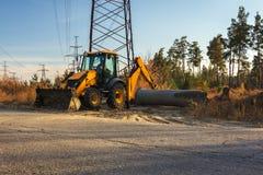 Dangerous job digger under high-voltage power line Stock Photography