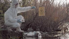 Dangerous job, hazmat biologist into protective clothing taking infected water sample in test tubes for examining in
