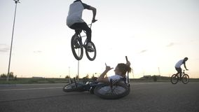 Dangerous jump performed by experienced cool biker over his relaxed friend sitting down with his bike in slow motion -. Dangerous jump performed by experienced stock video footage