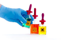 Dangerous lab Chemicals. Three labelled lab dropper bottles, green toxic, orange corrosive, yellow irritant.  With blue gloved hand Stock Image