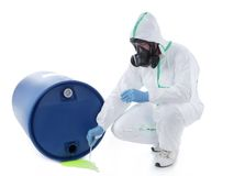 Dangerous leak. Man wearing protective suit and respirator sampling dangerous chemical liquid leaking from blue container Stock Photo