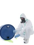 Dangerous leak. Man wearing protective suit and respirator sampling dangerous chemical liquid leaking from blue container Royalty Free Stock Photo