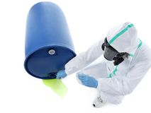 Dangerous leak. Man wearing protective suit and respirator sampling dangerous chemical liquid leaking from blue container Stock Image