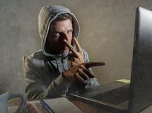 Dangerous looking hacker man in hoodie hacking internet computer system pointing his eyes warning about his ability to break passw. Dangerous looking hacker man stock photography