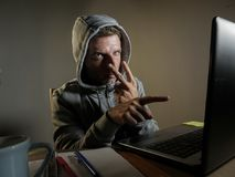 Dangerous looking hacker man in hoodie hacking internet computer system pointing his eyes warning about his ability to break passw. Dangerous looking hacker man stock photo