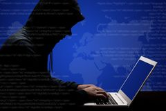 Dangerous male hacker in black hoody works solving online password code on laptop computer, keyboards information, tries t. O break system, poses sideways royalty free stock photo