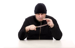 Dangerous man with a big knife. Dangerous man in black clothes sits with a big knife Royalty Free Stock Photo