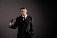 Dangerous man in black and a gun Royalty Free Stock Image