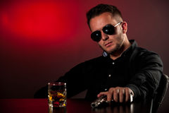 Dangerous man with a gun. Sitting in dark room with glass of alcohol on table Royalty Free Stock Photos