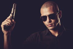 Dangerous man with a gun. Standing in dark room Stock Photos