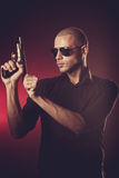 Dangerous man with a gun. And sunglasses Stock Photos