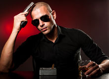 Dangerous man with a gun and sunglasses. Sitting in dark room, drinking and smoking Royalty Free Stock Image