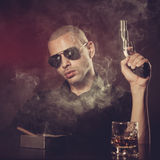 Dangerous man with a gun. And sunglasses smoking and drinking in dark room Royalty Free Stock Image