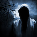 Dangerous man hiding under the hood. In the dark night forest Stock Photos