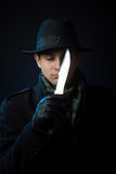Dangerous man with a knife. A man in black clothing with closed eyes holding a knife, studio shot, dark background Royalty Free Stock Photography