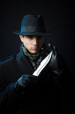 Dangerous man with a knife. A man in black clothing holding a knife, studio shot, dark background Royalty Free Stock Photo
