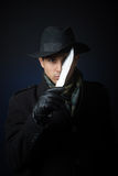 Dangerous man with a knife. A man in black clothing with a knife looking at camera, studio shot, dark background Royalty Free Stock Image