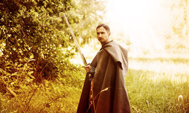 Dangerous man with medieval sword. Fantasy portrait of handsome dangerous man with medieval sword Royalty Free Stock Photos