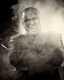 Dangerous man with scary face smoking cigar. Royalty Free Stock Images