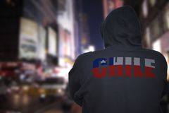 Dangerous man standing on a city street with black hoodie with text chile on his back stock images