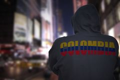 Dangerous man standing on a city street with black hoodie with text colombia on his back stock photography