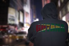 Dangerous man standing on a city street with black hoodie with text guyana on his back stock image