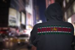 Dangerous man standing on a city street with black hoodie with text suriname on his back royalty free stock photo