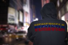 Dangerous man standing on a city street with black hoodie with text venezuela on his back stock image