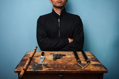 Dangerous man with various weapons. At old desk Stock Photography