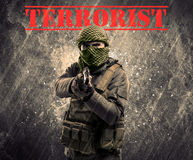 Dangerous masked and armed man with terrorist sign on grungy background. Portrait of dangerous masked and armed man with terrorist sign on grungy background royalty free stock photo