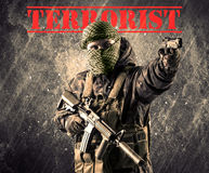 Dangerous masked and armed man with terrorist sign on grungy bac Stock Photography