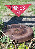 Dangerous mines sign. A dangerous mines sign pointing at an old, rusty mine below Stock Photos