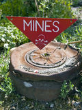 Dangerous mines sign. A dangerous mines sign pointing at an old, rusty mine below Royalty Free Stock Images