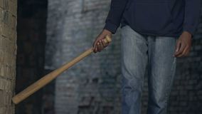 Dangerous mixed-race teen hooligan with baseball bat walking abandoned building. Stock footage stock footage