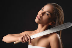 Dangerous mulatto woman carrying big sword Stock Image