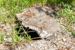 Dangerous opened manhole hole covered with damaged cracked concrete panel, danger for people and animals in the park.  Stock Photo