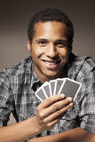 Dangerous opponent. Smiling dark-skinned young man holding playing cards Royalty Free Stock Photo
