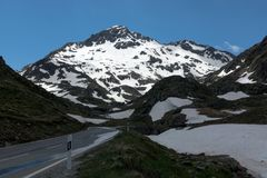 Dangerous turned road high in the Alps between melting snow Stock Photos