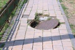 Dangerous pavement. Dangerous sidewalk - pedestrian danger with crooked manhole cover. Insurance claim risk Stock Image
